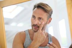 Applaying κρέμα αντι-γήρανσης ατόμων στο πρόσωπό του Στοκ φωτογραφία με δικαίωμα ελεύθερης χρήσης