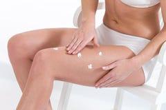 Applaying moisturizin κρέμα γυναικών στα πόδια Στοκ φωτογραφία με δικαίωμα ελεύθερης χρήσης