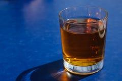 Apple ή διευκρινισμένος σταφύλι χυμός στο γυαλί στο μπλε Στοκ φωτογραφίες με δικαίωμα ελεύθερης χρήσης