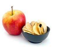 Apple ή πατατάκια - επιλογές πρόχειρων φαγητών Στο λευκό Στοκ Φωτογραφία