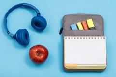 Apple, ακουστικά και ανοικτό βιβλίο άσκησης στην περίπτωση τσάντα-μολυβιών με Στοκ Εικόνα