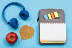 Apple, ακουστικά, ξηρό φύλλο, ανοικτό βιβλίο άσκησης στο ασβέστιο τσάντα-μολυβιών Στοκ φωτογραφία με δικαίωμα ελεύθερης χρήσης