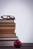 Apple από τα βιβλία με eyeglass στον πίνακα Στοκ Εικόνες