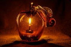 Apple από το γυαλί μέσω του οποίου μπορείτε να δείτε ένα κερί Στοκ Φωτογραφίες