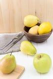 Apple, αχλάδια λεμόνι στο ξύλινο κύπελλο Άσπρη ξύλινη ανασκόπηση Στοκ εικόνα με δικαίωμα ελεύθερης χρήσης