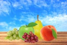 Apple, αχλάδι, ροδάκινο και σταφύλι στον ξύλινο πίνακα άνω του θολωμένου μπλε s Στοκ Φωτογραφίες
