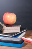 Apple, βιβλία και κιμωλίες με το υπόβαθρο πινάκων Στοκ Φωτογραφία