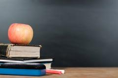 Apple, βιβλία και κιμωλίες με το υπόβαθρο πινάκων Στοκ εικόνα με δικαίωμα ελεύθερης χρήσης
