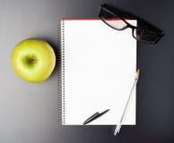 Apple, γυαλιά και βιβλίο σημειώσεων Στοκ Εικόνες