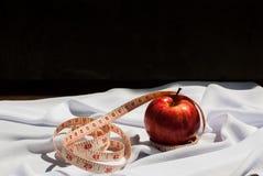 Apple και ένα μέτρο ταινιών πέρα από ένα άσπρο υπόβαθρο Στοκ Φωτογραφία