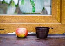 Apple και ένα φλυτζάνι με το ξύλινο παράθυρο Στοκ Εικόνα
