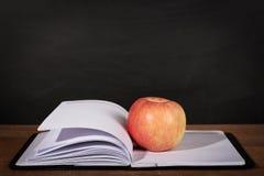 Apple και ανοιγμένο βιβλίο με το υπόβαθρο πινάκων Στοκ εικόνες με δικαίωμα ελεύθερης χρήσης