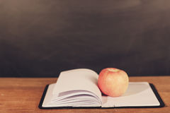 Apple και ανοιγμένο βιβλίο με το υπόβαθρο πινάκων Στοκ Φωτογραφίες