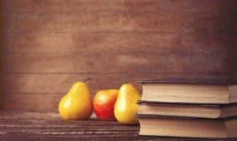 Apple και αχλάδι κοντά στα βιβλία Στοκ Εικόνες