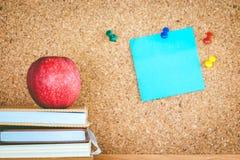 Apple και βιβλία με την κολλώδη σημείωση για τον πίνακα φελλού Στοκ φωτογραφία με δικαίωμα ελεύθερης χρήσης