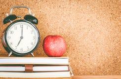 Apple και βιβλία με το ξυπνητήρι στον πίνακα φελλού Στοκ φωτογραφία με δικαίωμα ελεύθερης χρήσης