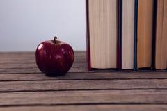 Apple και βιβλία που τακτοποιούνται στον ξύλινο πίνακα Στοκ Φωτογραφία