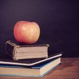 Apple και βιβλία με το υπόβαθρο πινάκων Στοκ Εικόνες