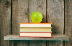 Apple και βιβλία σε ένα ξύλινο ράφι Στοκ Εικόνες