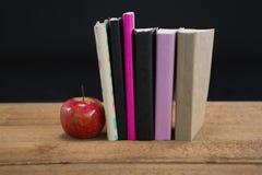 Apple και βιβλία στον ξύλινο πίνακα Στοκ Εικόνα