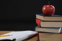 Apple και βιβλίο στον ξύλινο πίνακα Στοκ Εικόνες