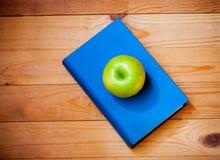 Apple και βιβλίο στο ξύλινο υπόβαθρο Τοπ όψη Στοκ φωτογραφίες με δικαίωμα ελεύθερης χρήσης