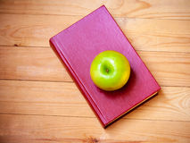 Apple και βιβλίο στο ξύλινο υπόβαθρο Τοπ όψη Στοκ φωτογραφία με δικαίωμα ελεύθερης χρήσης