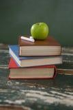 Apple και κιμωλίες στο σωρό των βιβλίων Στοκ φωτογραφία με δικαίωμα ελεύθερης χρήσης