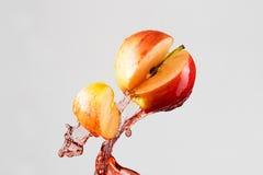 Apple και κόκκινος παφλασμός χυμού που απομονώνονται σε ένα γκρίζο υπόβαθρο Στοκ Εικόνα