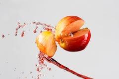 Apple και κόκκινος παφλασμός χυμού που απομονώνονται σε ένα γκρίζο υπόβαθρο Στοκ Εικόνες