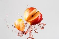Apple και κόκκινος παφλασμός χυμού που απομονώνονται σε ένα γκρίζο υπόβαθρο Στοκ Φωτογραφία