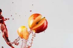 Apple και κόκκινος παφλασμός χυμού που απομονώνονται σε ένα γκρίζο υπόβαθρο Στοκ εικόνες με δικαίωμα ελεύθερης χρήσης