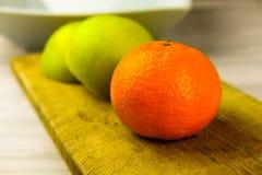 Apple και μανταρίνι στον τέμνοντα πίνακα που προετοιμάζει τη σαλάτα φρούτων Στοκ Φωτογραφίες