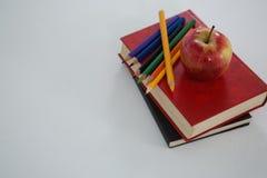 Apple και μολύβια χρώματος στο βιβλίο στο άσπρο υπόβαθρο Στοκ Φωτογραφία