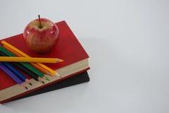 Apple και μολύβι χρώματος στο βιβλίο Στοκ Εικόνα