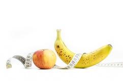 Apple και μπανάνα με τη μέτρηση της ταινίας Στοκ Εικόνες