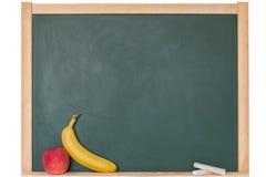 Apple και μπανάνα μπροστά από έναν πίνακα Στοκ φωτογραφία με δικαίωμα ελεύθερης χρήσης