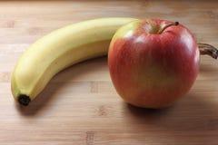 Apple και μπανάνα σε έναν πίνακα Στοκ φωτογραφίες με δικαίωμα ελεύθερης χρήσης
