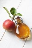 Apple και μπουκάλι glas φύλλων που γεμίζουν με το ξίδι μηλίτη μήλων Στοκ Φωτογραφία