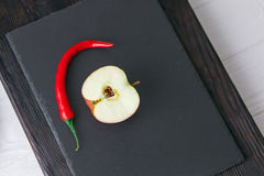 Apple και πιπέρι στον πίνακα πετρών Στοκ εικόνες με δικαίωμα ελεύθερης χρήσης