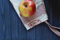 Apple και ποδιά στον πίνακα στην κουζίνα Στοκ εικόνες με δικαίωμα ελεύθερης χρήσης