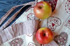 Apple και ποδιά στον πίνακα στην κουζίνα Στοκ Εικόνες