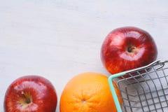 Apple και πορτοκάλι με το καλάθι αγορών Στοκ Εικόνες