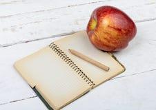 Apple και σημειωματάριο σε έναν πίνακα Στοκ εικόνες με δικαίωμα ελεύθερης χρήσης