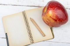 Apple και σημειωματάριο σε έναν πίνακα Στοκ εικόνα με δικαίωμα ελεύθερης χρήσης