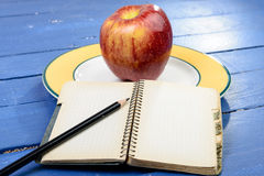 Apple και σημειωματάριο σε έναν πίνακα Στοκ φωτογραφία με δικαίωμα ελεύθερης χρήσης