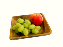 Apple και σταφύλια σε ένα ξύλινο πιάτο Στοκ Φωτογραφίες