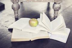 Apple και τέσσερα ανοικτά βιβλία σε ένα πάτωμα Στοκ Εικόνες