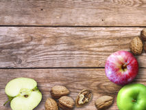 Apple και υπόβαθρο καρυδιών Ξηρά ξύλα καρυδιάς με το aple σε ένα ξύλινο υπόβαθρο Στοκ εικόνα με δικαίωμα ελεύθερης χρήσης
