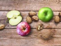 Apple και υπόβαθρο καρυδιών Ξηρά ξύλα καρυδιάς με το aple σε ένα ξύλινο υπόβαθρο Στοκ φωτογραφία με δικαίωμα ελεύθερης χρήσης